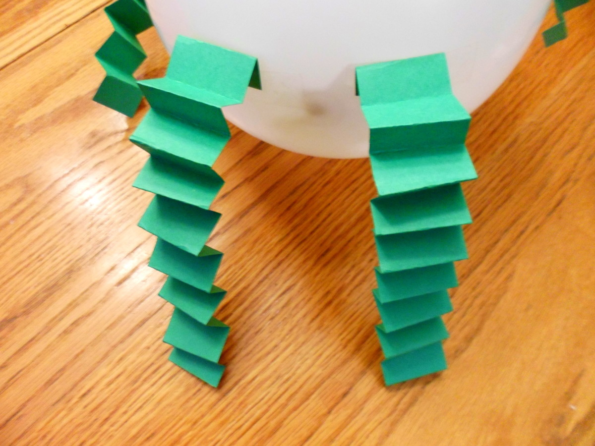 Bend pieces of construction paper back and forth to create arms and legs and tape to balloon.