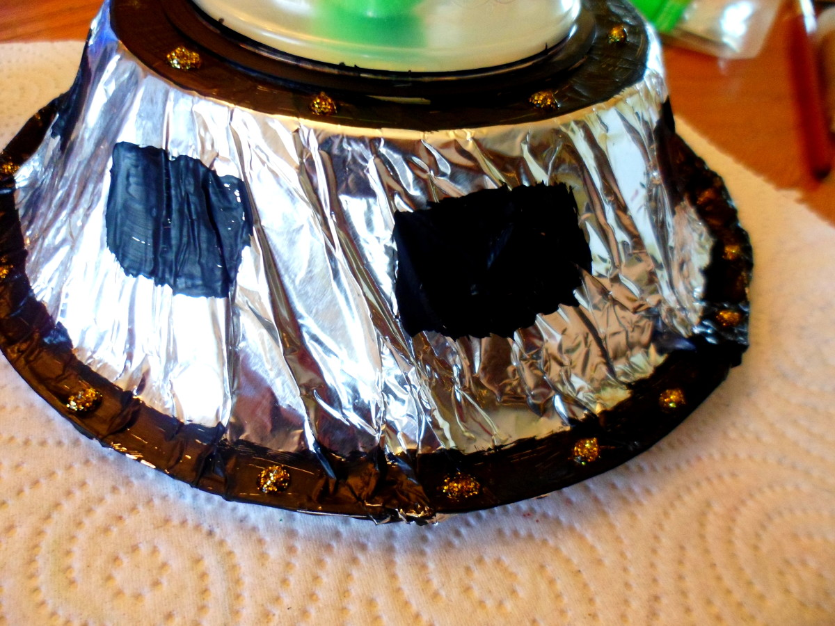 Use black paint and gold glitter glue to decorate the spaceship.