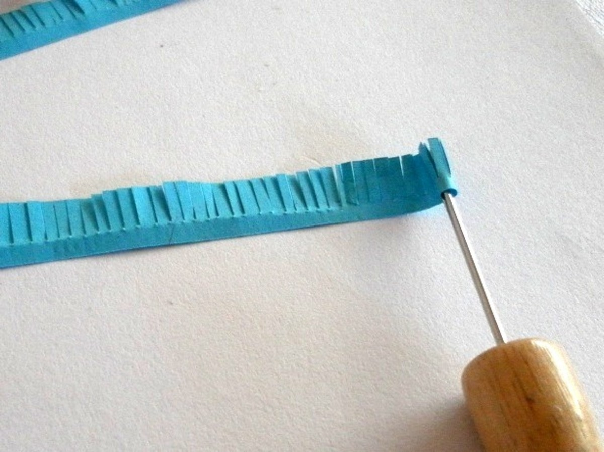 Roll the fringed paper into a tight coil with a quilling tool