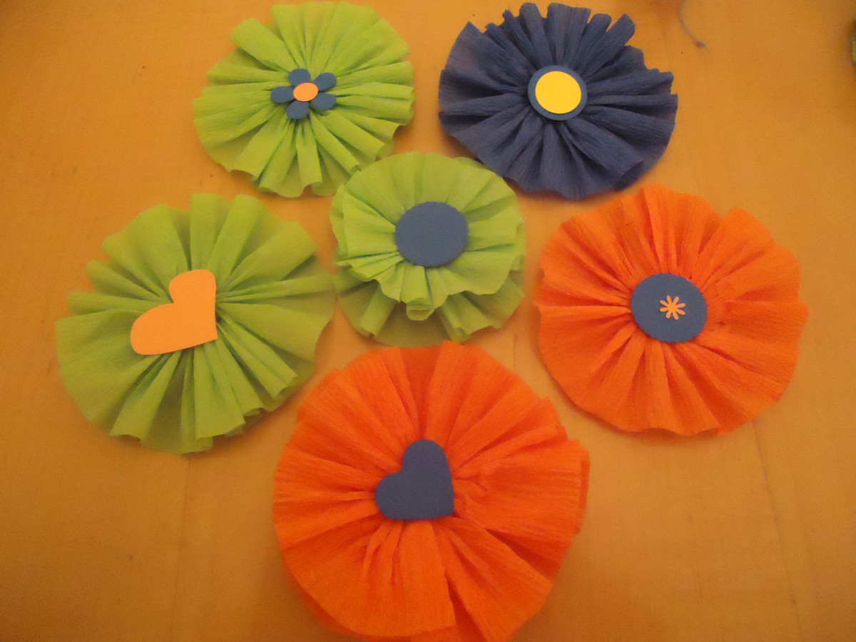 Rosettes embellished with paper shapes.