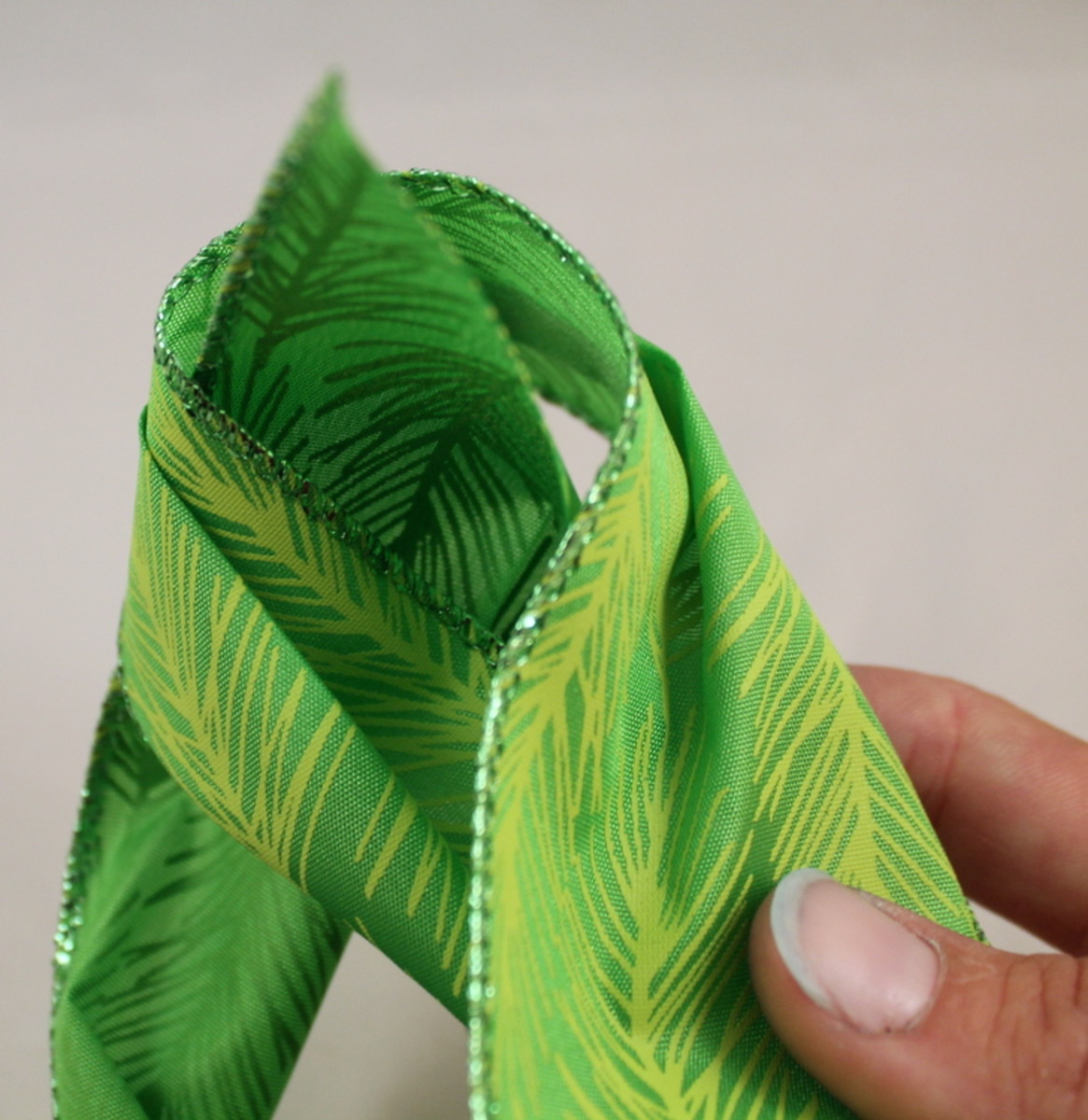 Using whichever end of the ribbon is 'on top' of the loop, bring the ribbon's end through the loop from front to back.