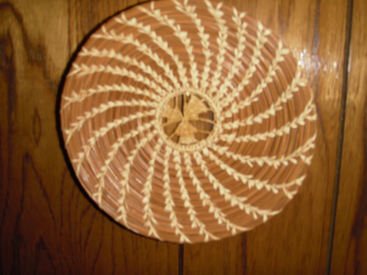 This decorative plate by J. Simpson has a slice of black walnut shell sewn into the starting coil.