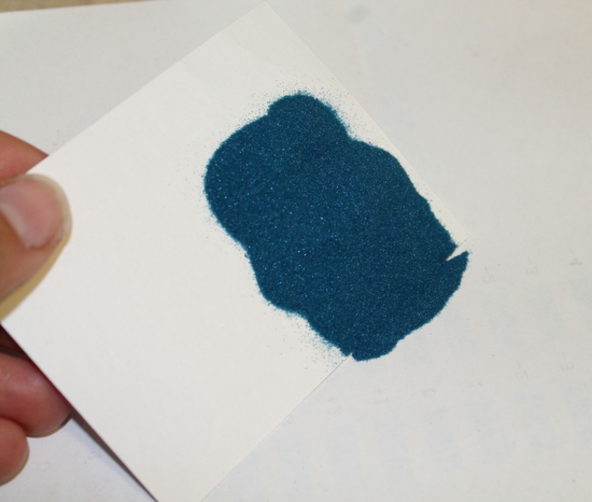 Pour the loose powder off onto a spare sheet of paper.