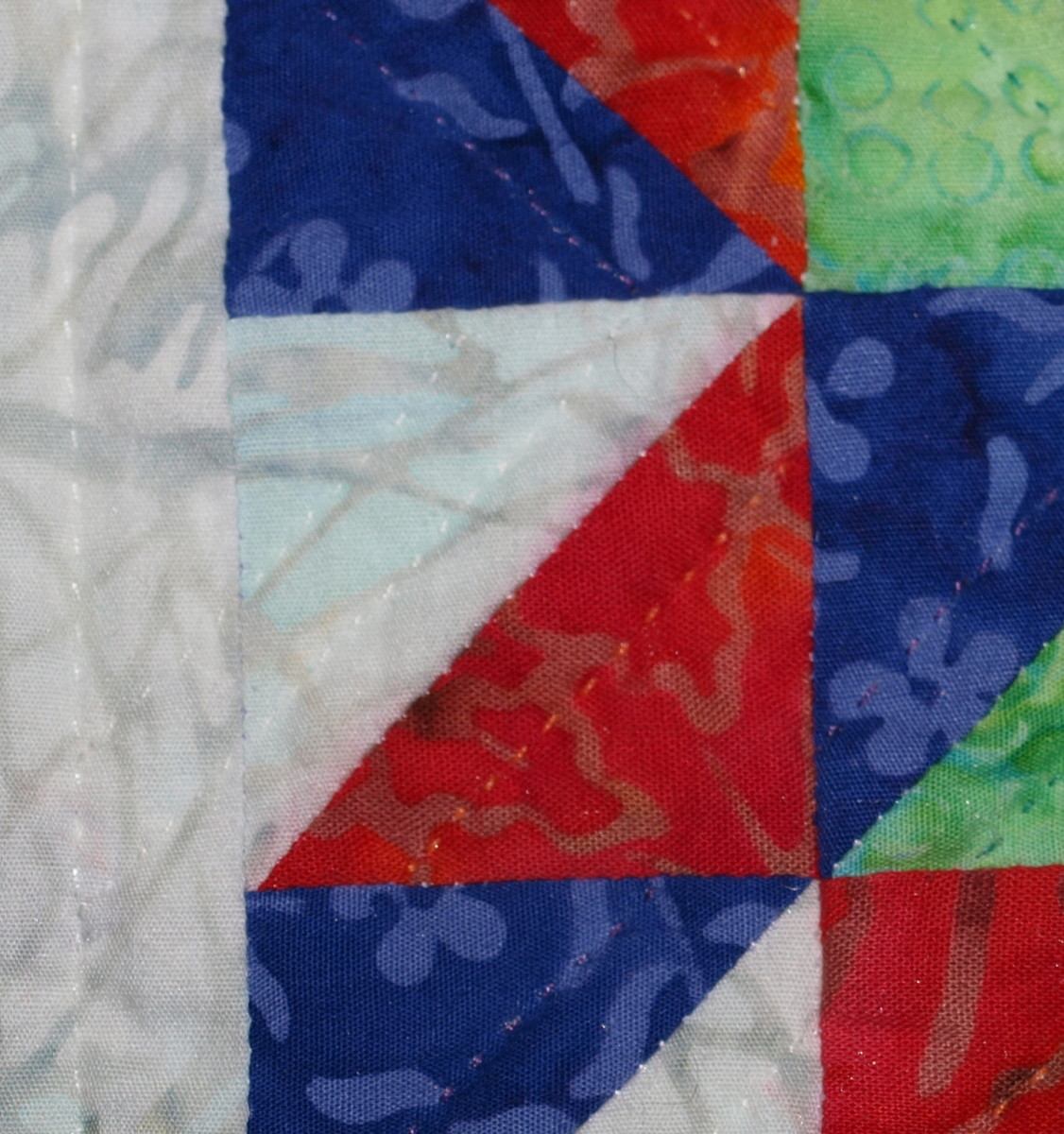 This quilt was spot cleaned and the red fabric ran when it got wet.  Look at the white fabric along the diagonal seam to see where the fabric bled.