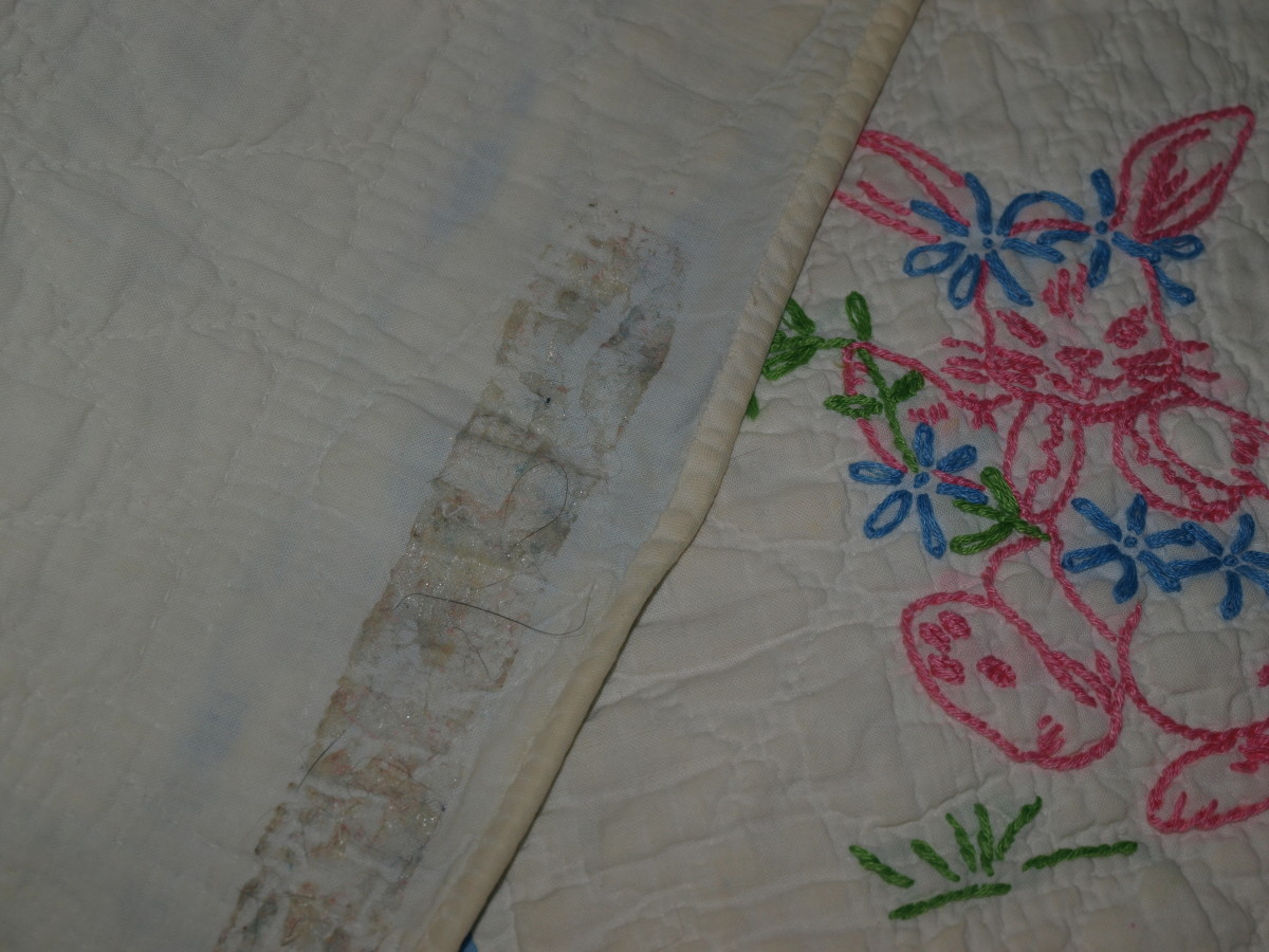 Antique quilt with damage from adhesive tape used to hang the quilt.  The tape was removed but the glue remained, as well as the tear that occurred when removing the tape.