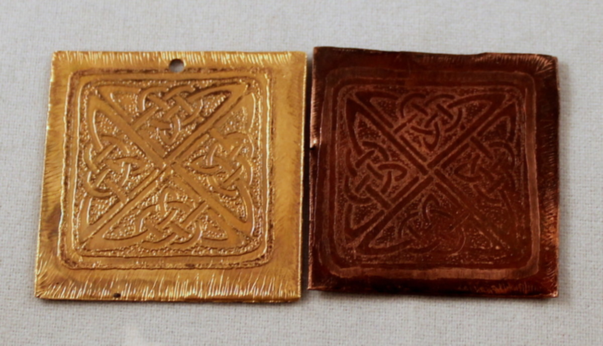 The pendant on the left is brass and has not been covered with a patina. The pendant on the right is copper and has been given a patina using liver of sulfur.