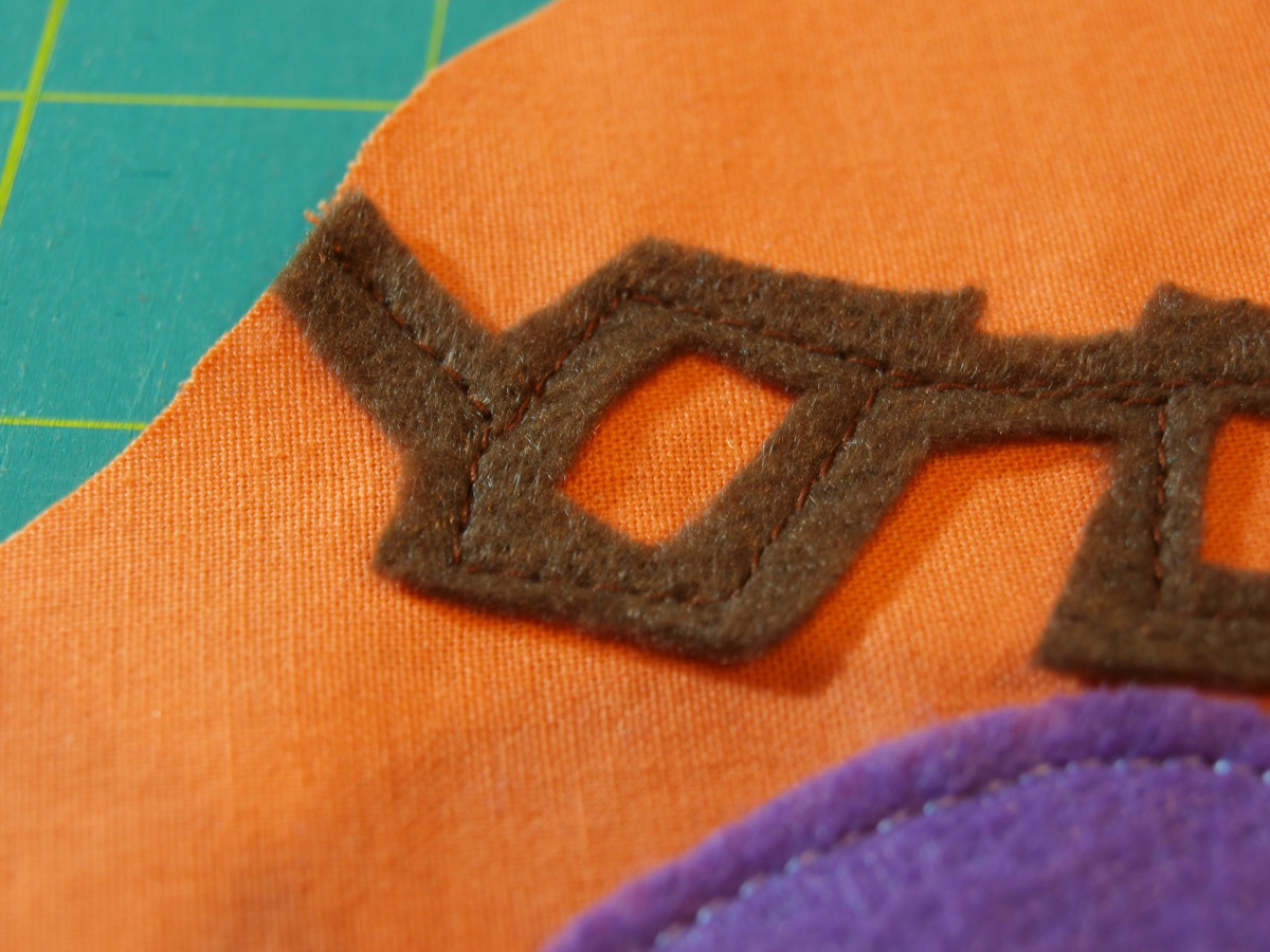 Sew pieces onto the front piece of the toy's body fabric.