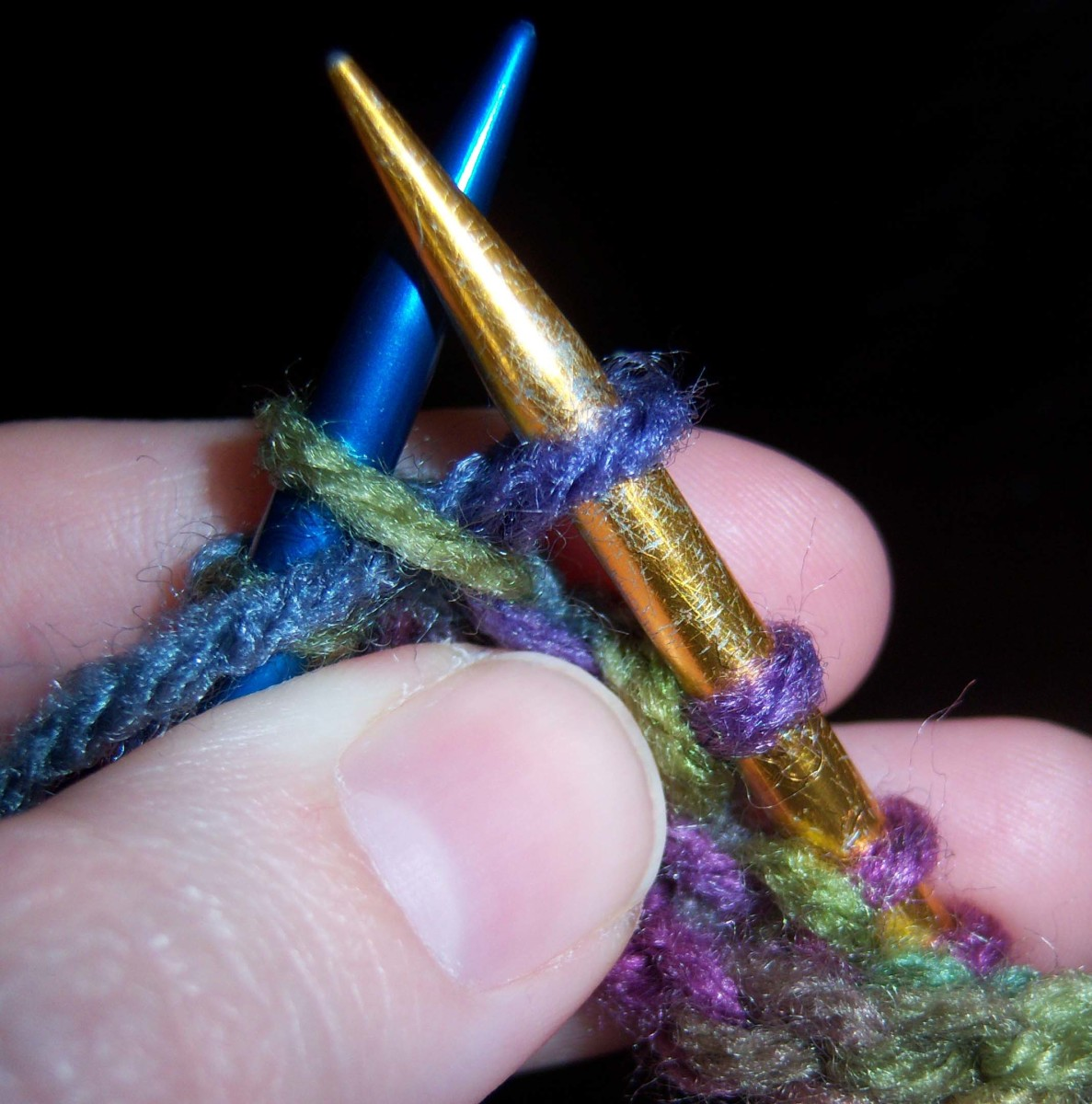 If you were going to only purl this stitch, you would let the green stitch slip from the blue needle.