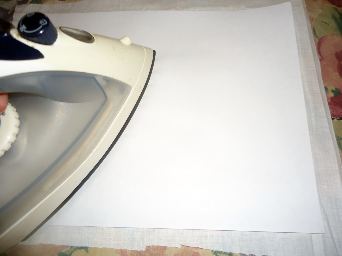 With shiny side down, iron the freezer paper to the fabric.