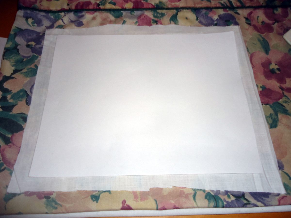 The freezer paper on top of the cut out piece of white fabric.