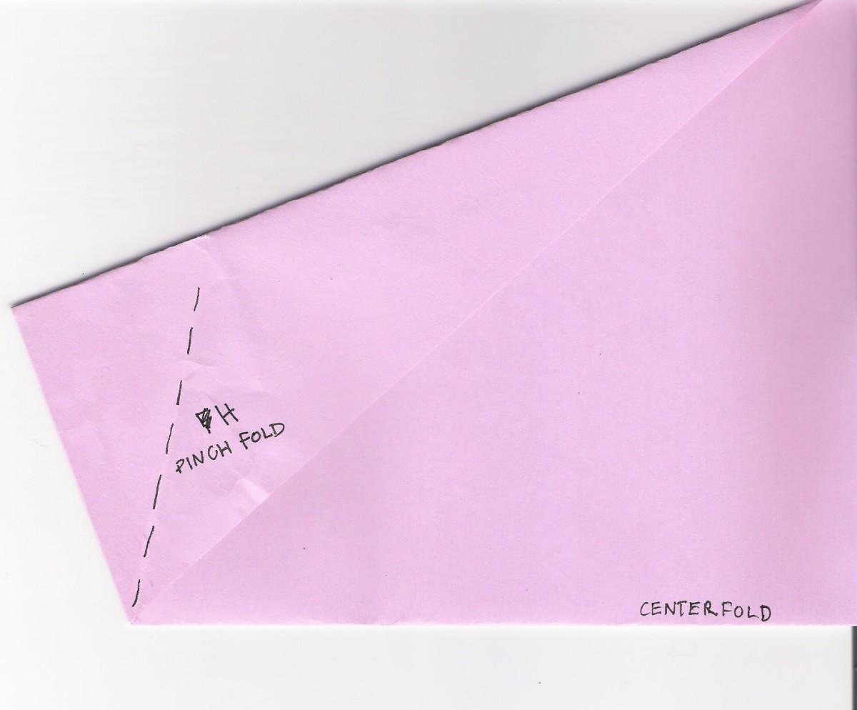 H. Fold the corner in half in a pinch fold.