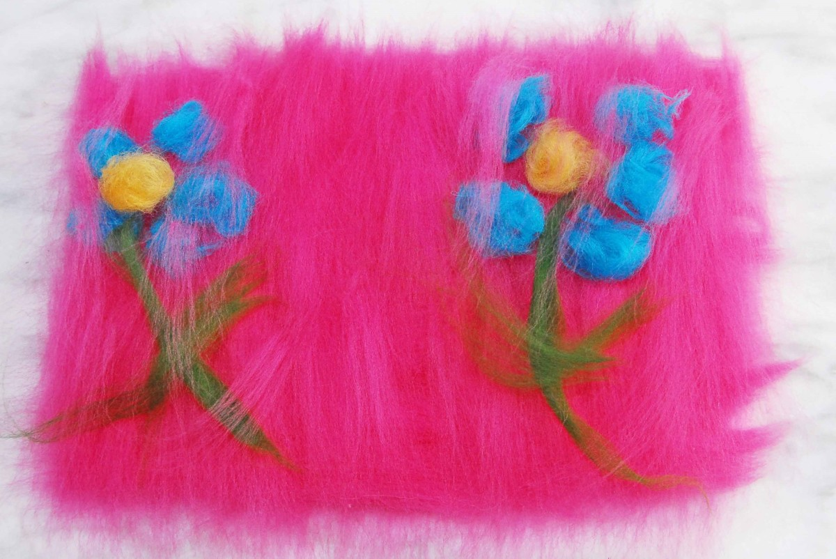 Flowers with small bits of pink fiber placed on top to help embed them to underneath layers