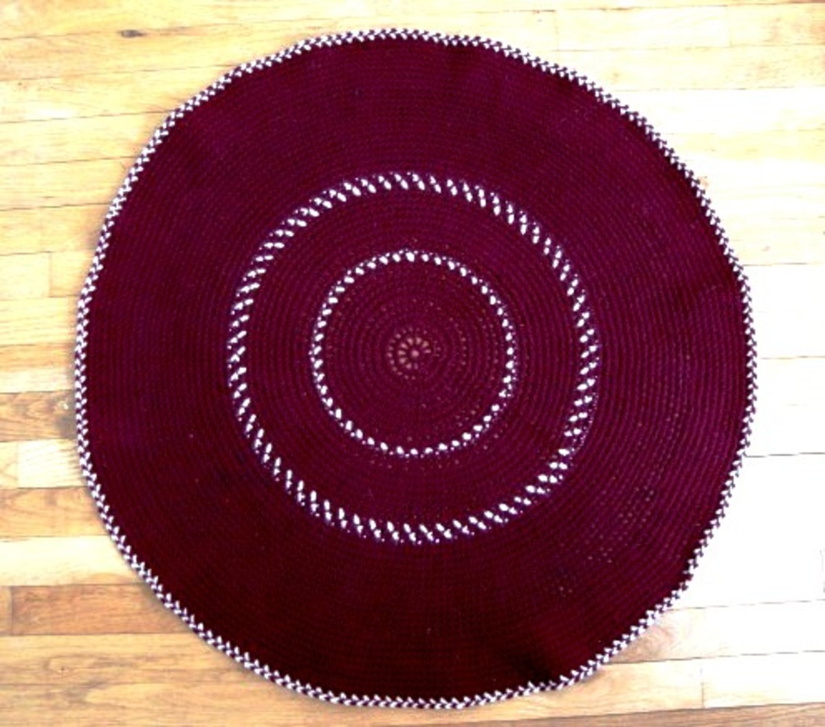 Crocheting a Round Rug in Maroon and Cream-Colored Yarn