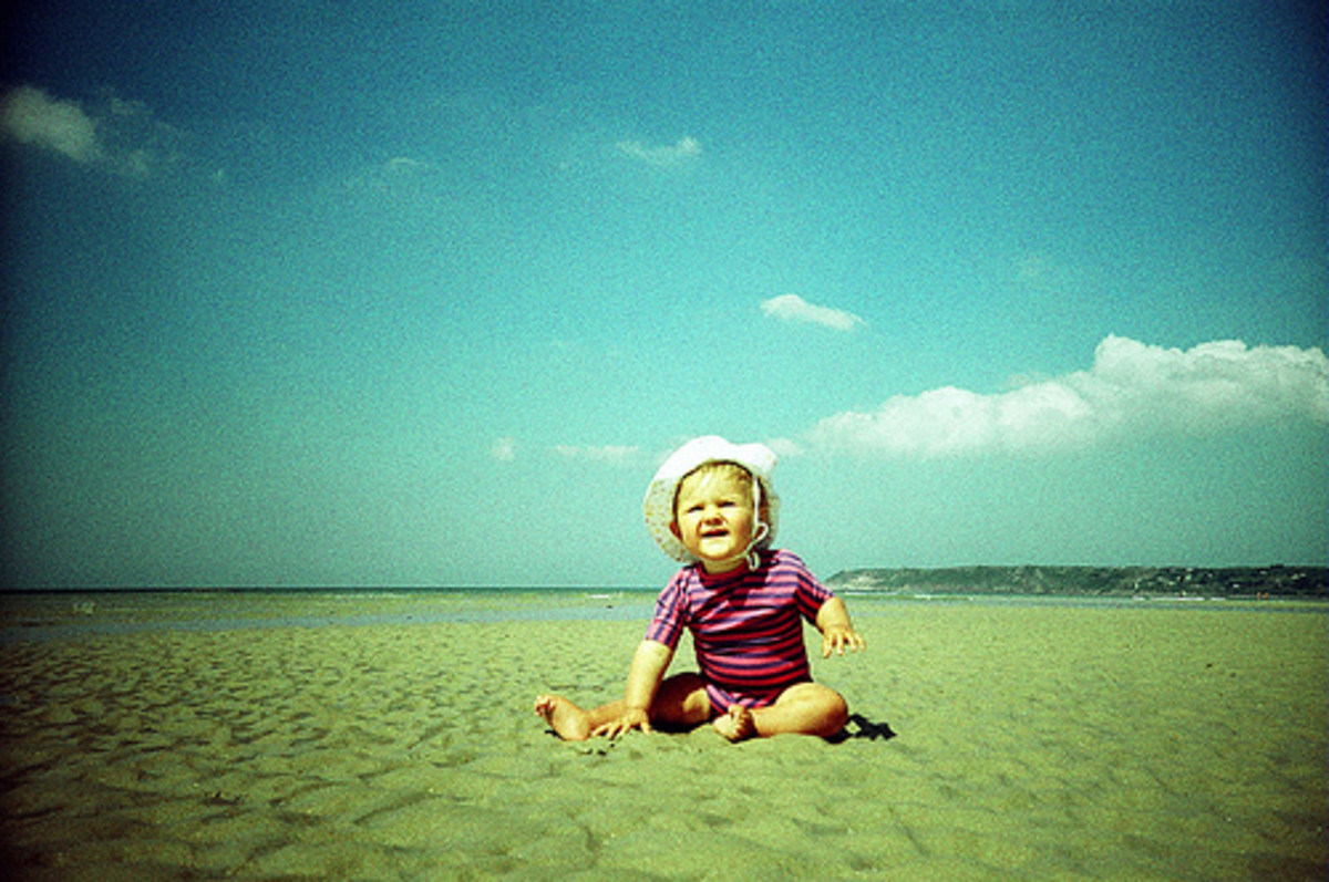The beach is a classic spot for a baby's first summer photo shoot.