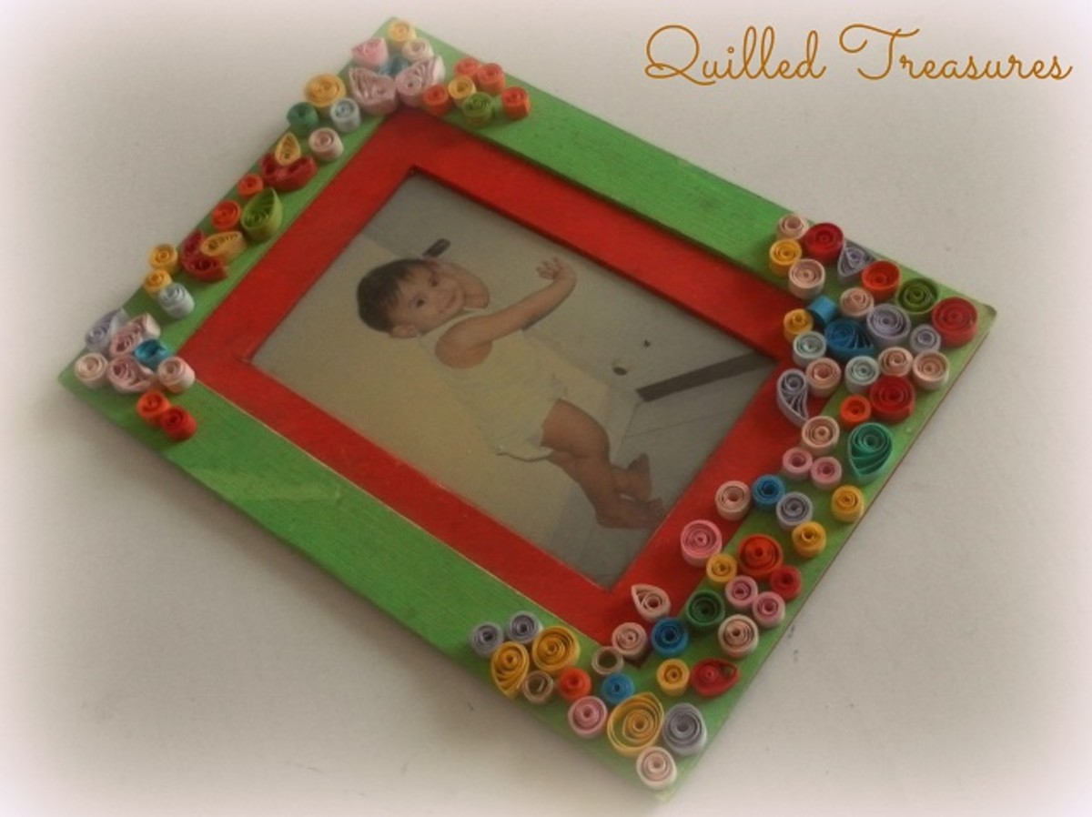 An old handmade photo frame decorated with paper quilling coils.