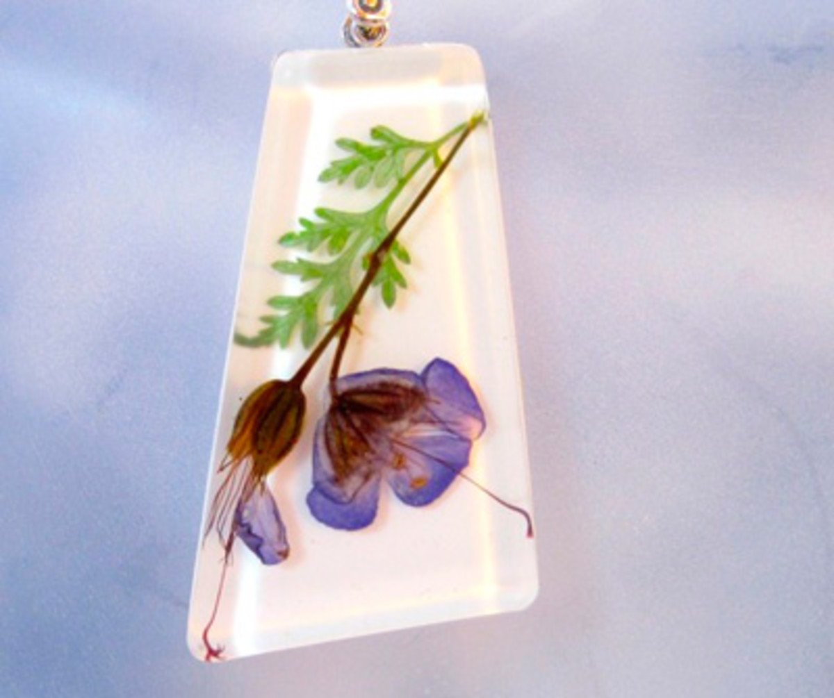 Pressed flowers set in resin as a pendant.