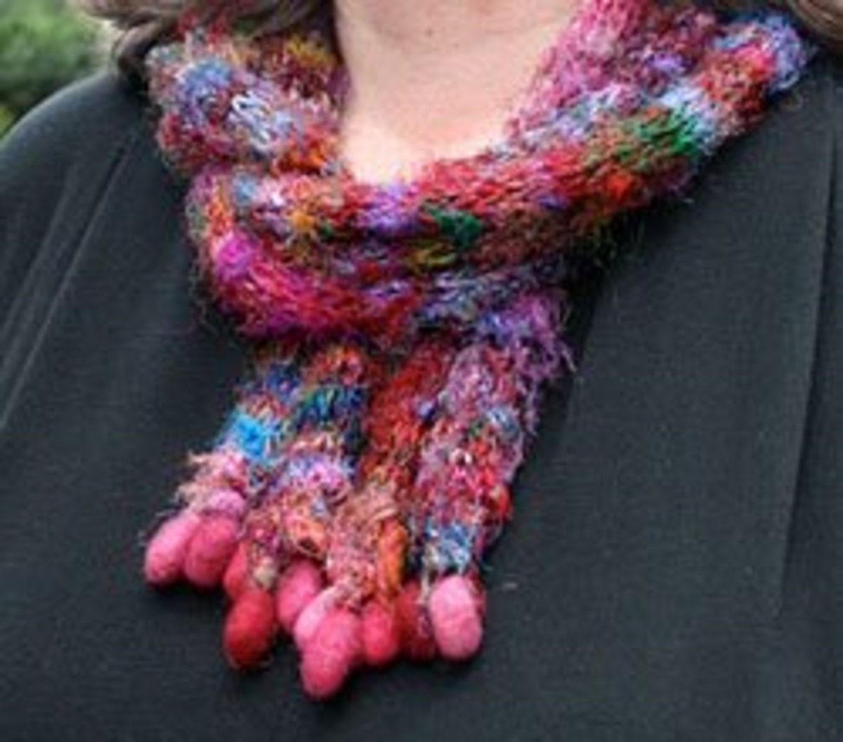 An unusual scarf, knitted in rounds, with dangly felted balls on the end.
