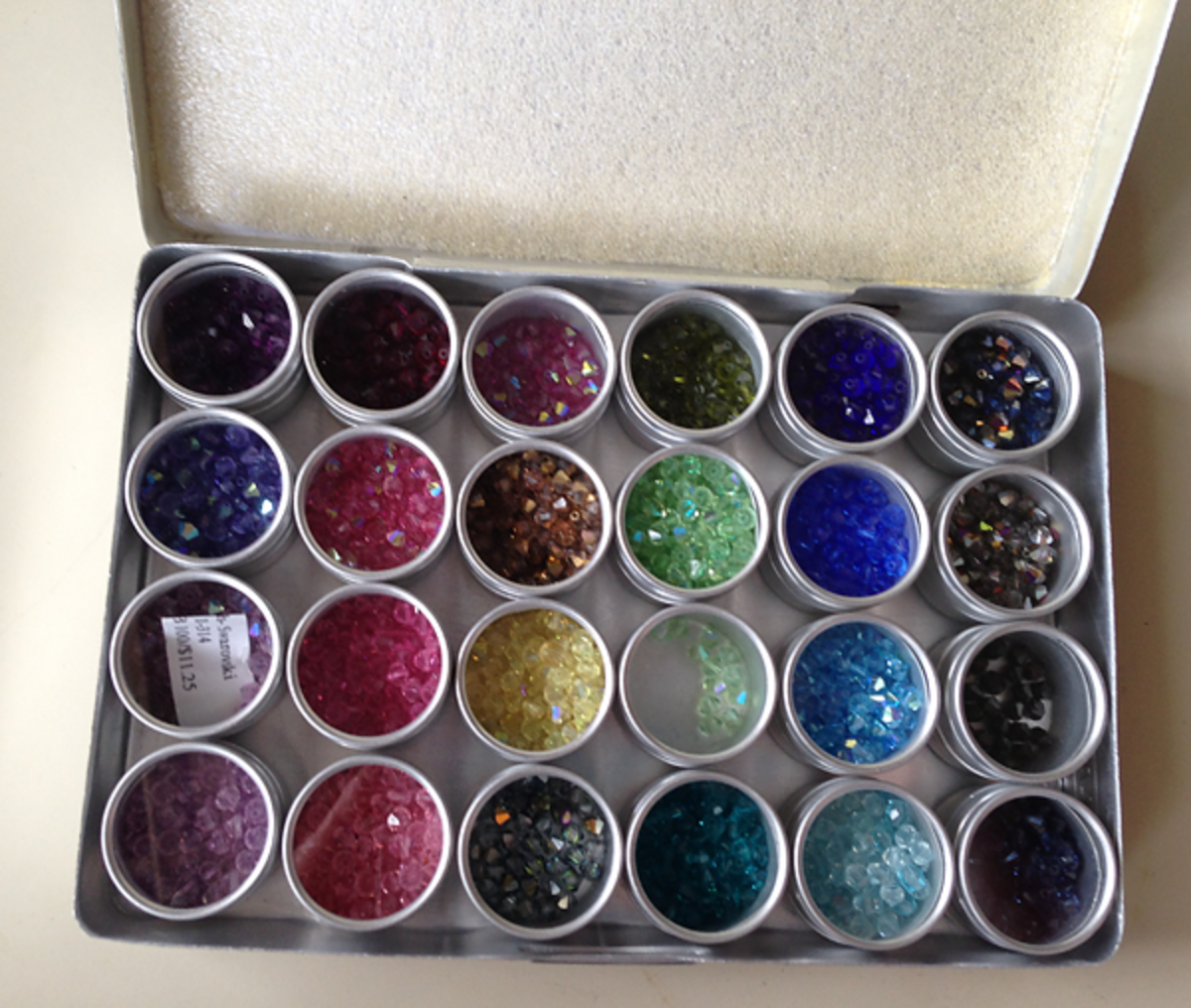 Photo of bead storage tins filled with Swarovski bicone crystals