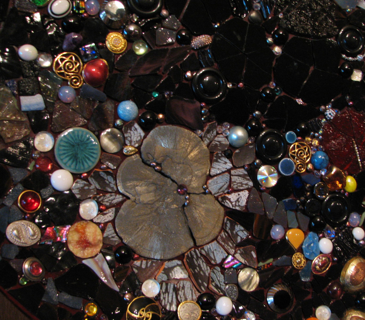 Outer space mosaic, contains an iron pyrite flower, glass globs, stained glass, glass cabochons, broken pottery, ceramic tile, costume jewelry, crystals, amethyst, pearls
