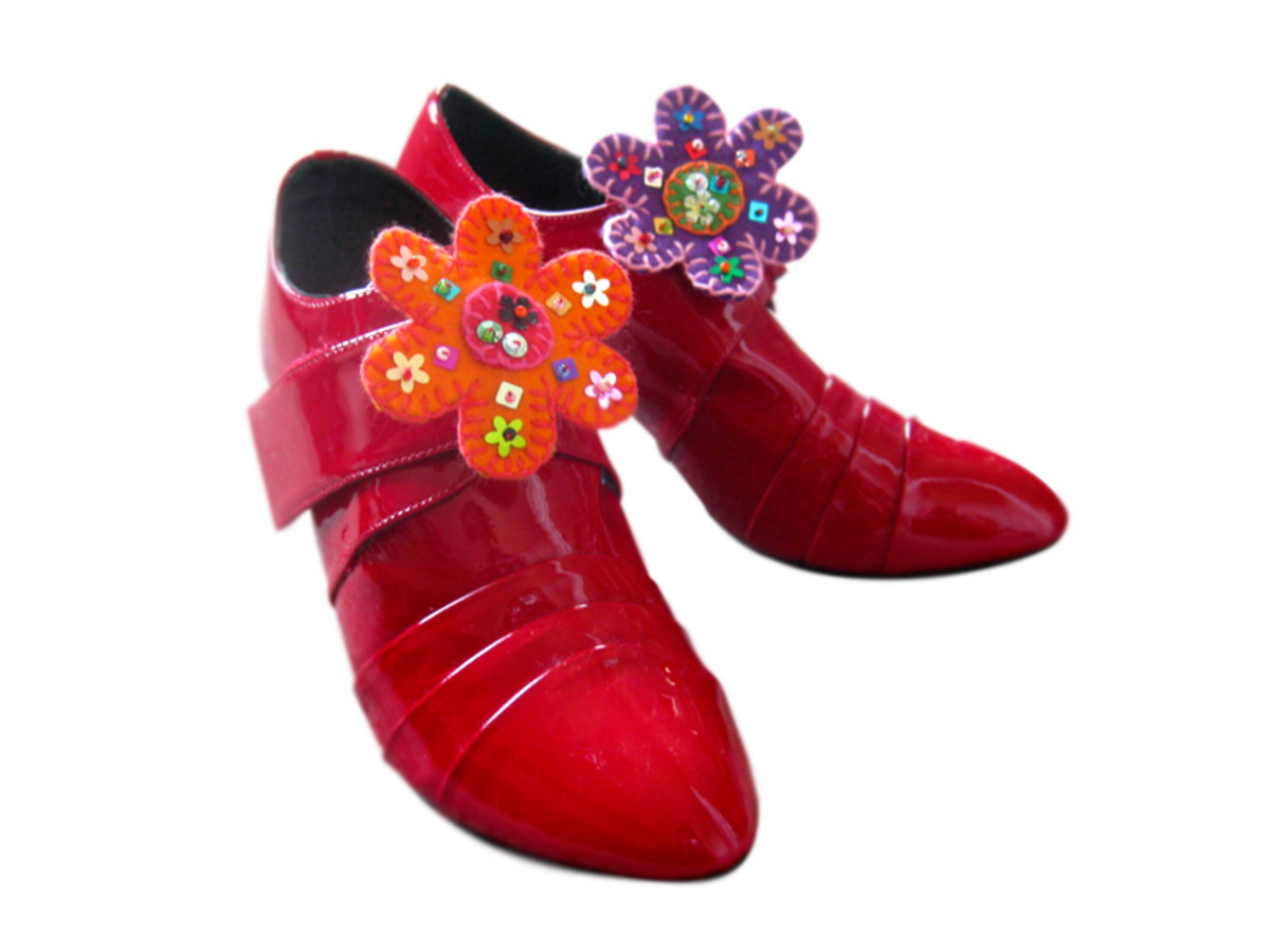 Add a large pelican clasp on the back of each flower, sewn on in similar manner to a brooch, so they can be added to shoes.