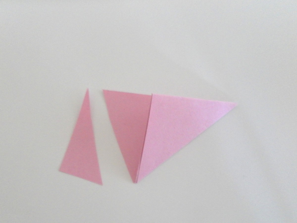 Take a pair of scissors and trim off part of the paper at the other end. Be careful not to cut the triangle.