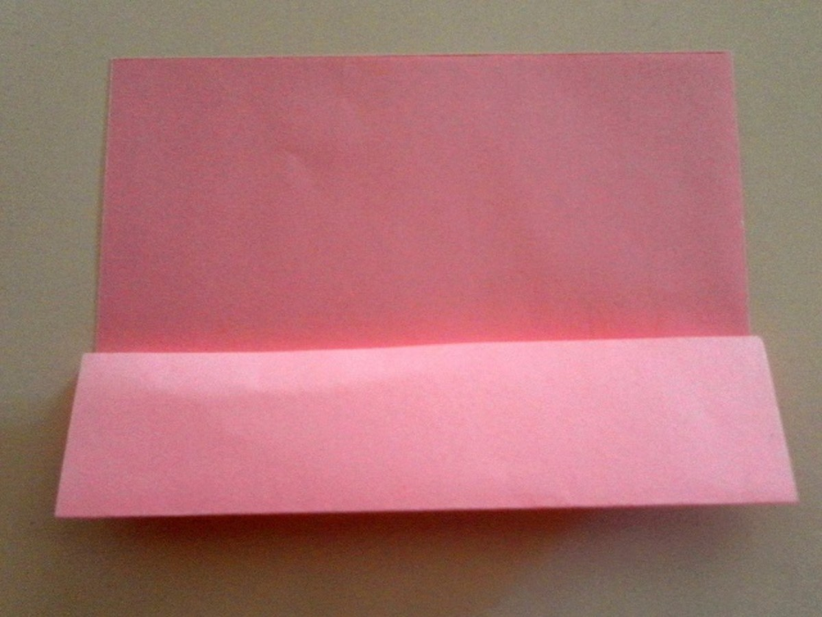 Unfold the paper and fold the edge of the bottom flap to the horizontal crease line in the centre.