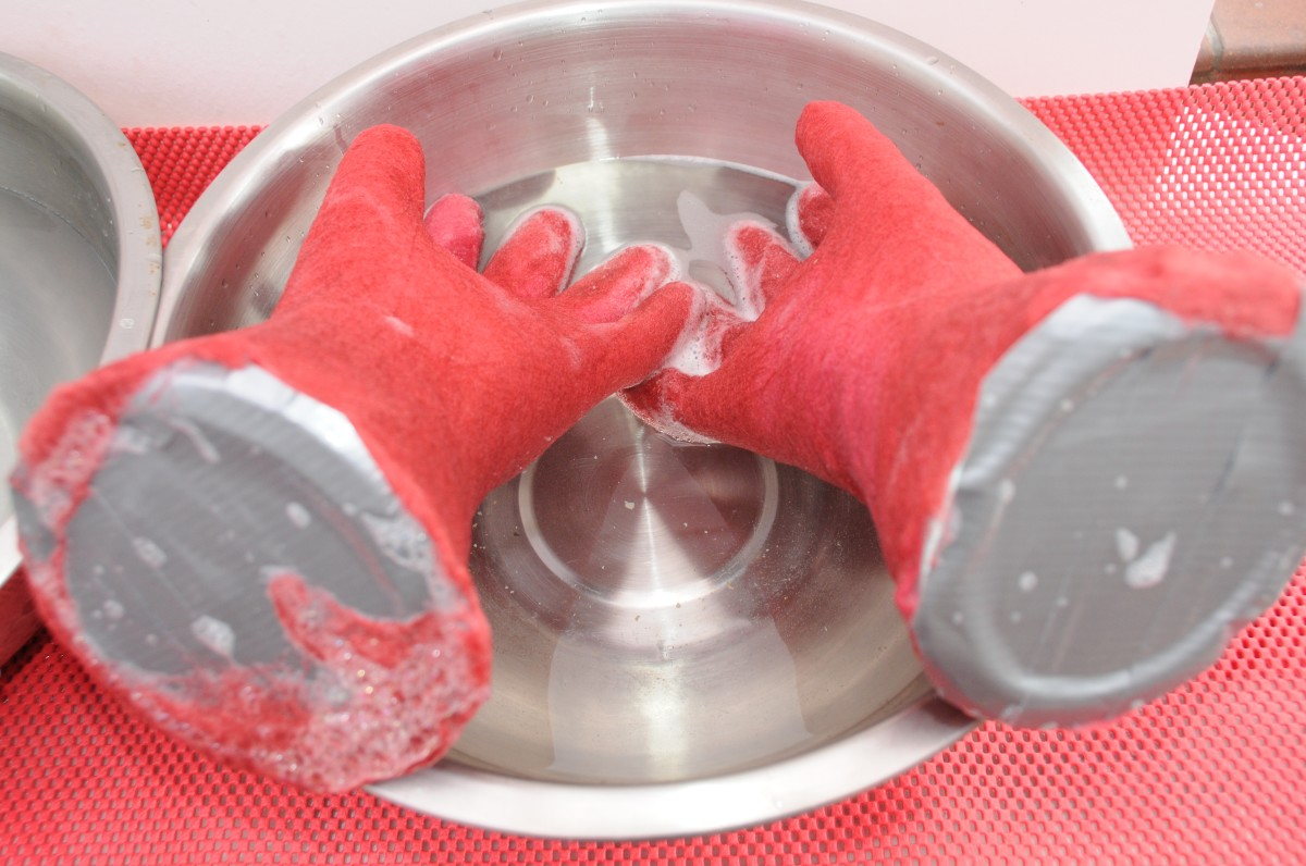 The rubber gloves are being dunked first in hot water and then in cold water.