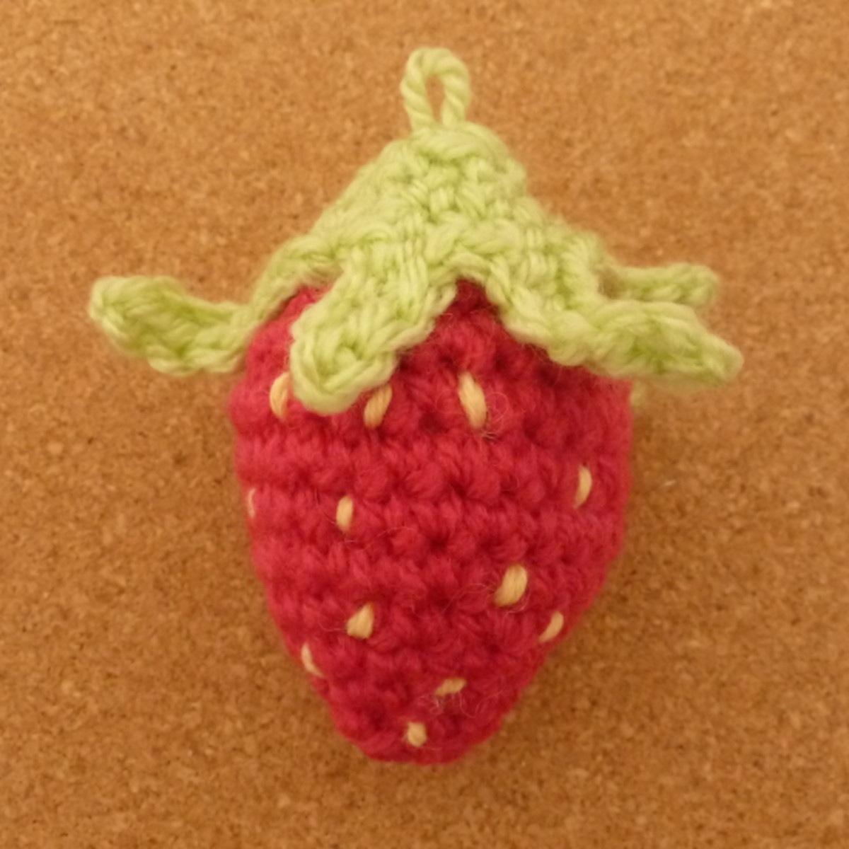 Making a yarn loop to hang the finished crochet strawberry piece on to a garland.