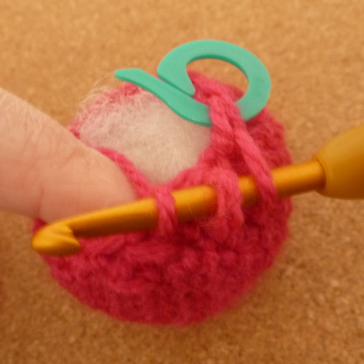 Crocheting a strawberry and getting near the top of the design.