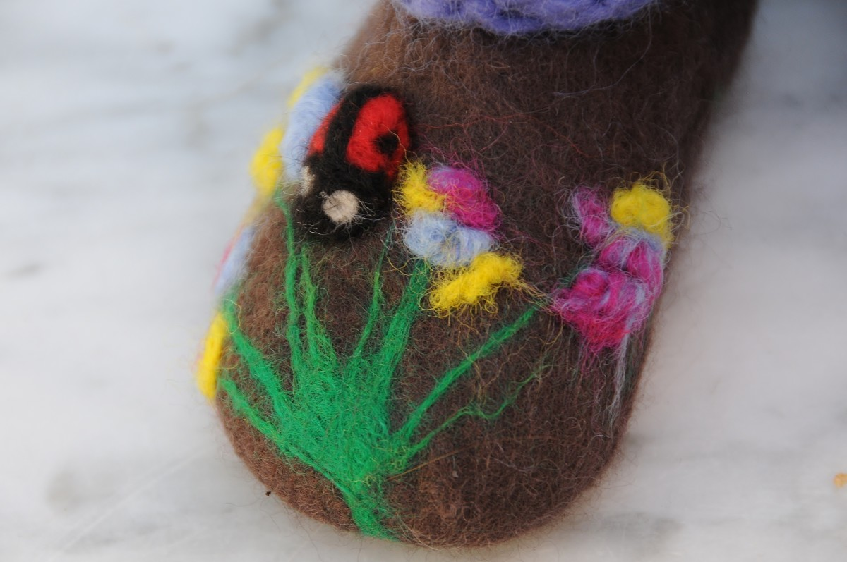 Needle felt any loose bits of wool to the slipper and add a little ladybird using black, red and white merino wool roving.