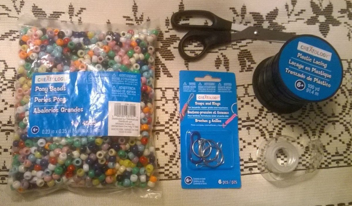 Pony beads, plastic lacing, scissors, tape and key ring / lanyard snap / carabiner.