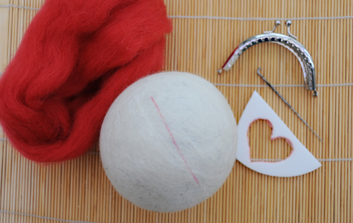 Items required for needle felting the heart and ladybugs onto the felted ball.