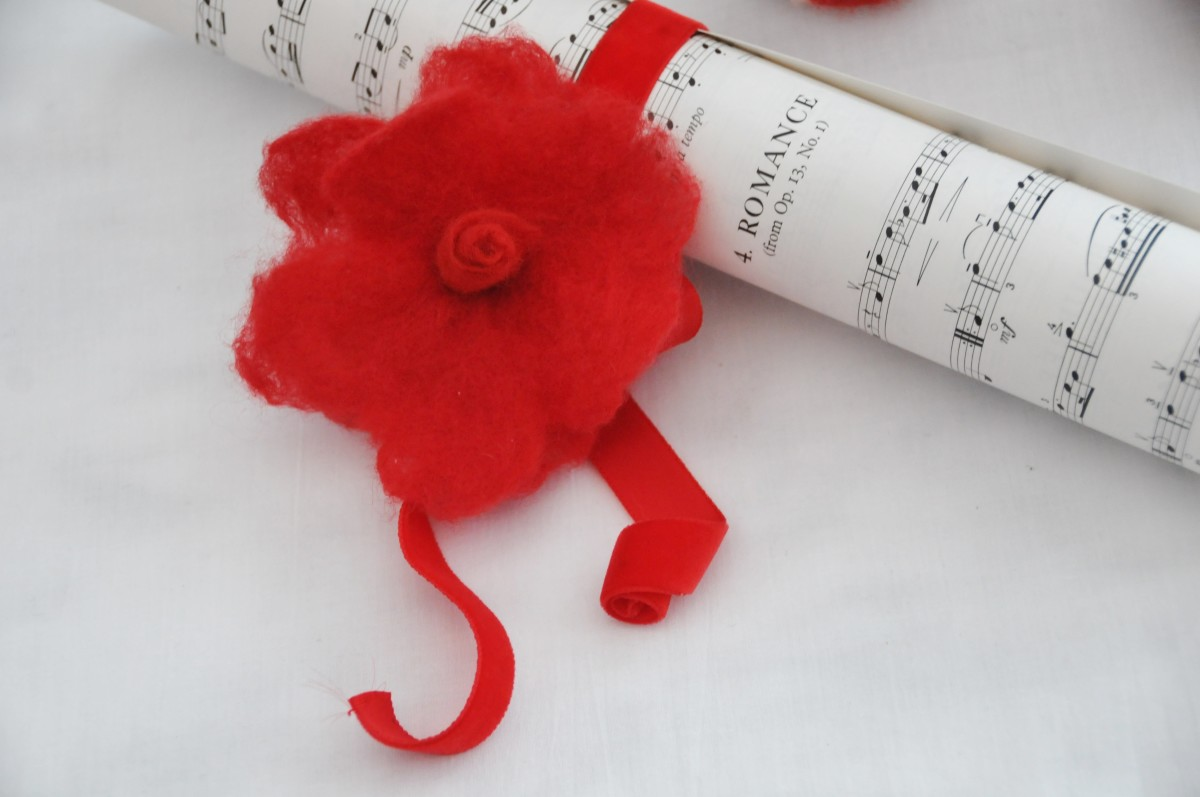 Music scroll and a red wet felted rose.