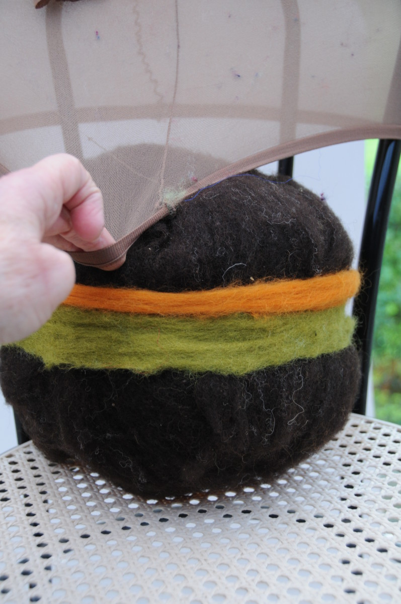 Putting the wool covered ball up into a pair of cut off tights
