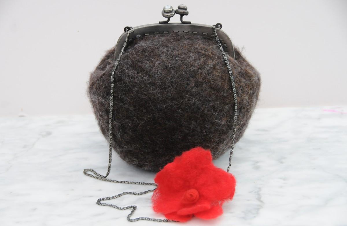 A completed shoulder bag with a felt flower