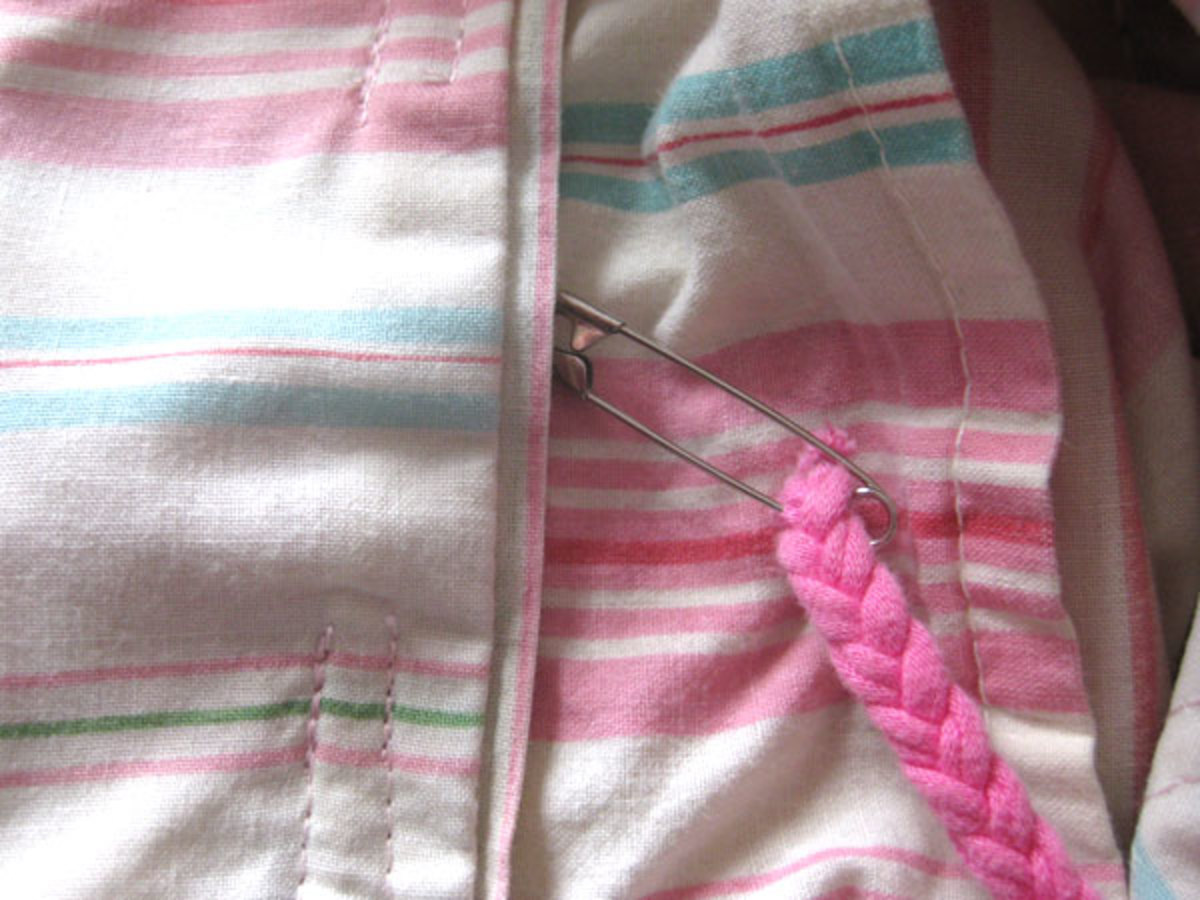 The safety pin (with cord attached) going into the opening of the drawstring hem.