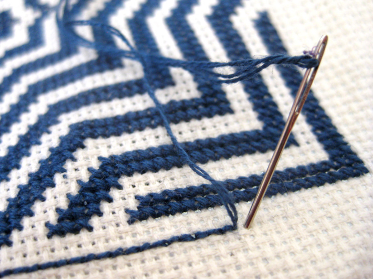 Step A: Point the embroidery needle down into the first stitch (one Aida square).