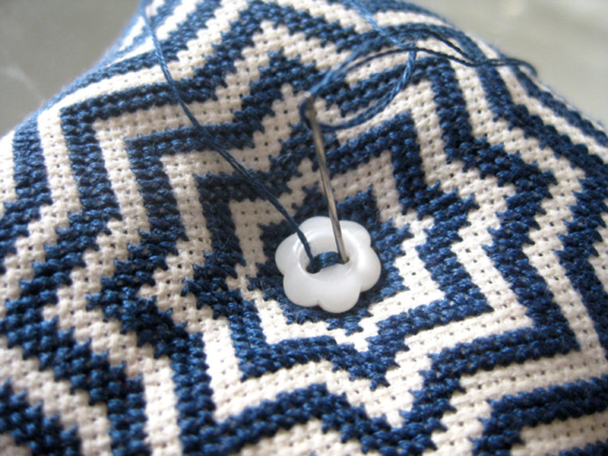 Sewing on one button (the needle passes through to the other side of the biscornu and sews on the second button at the same time).