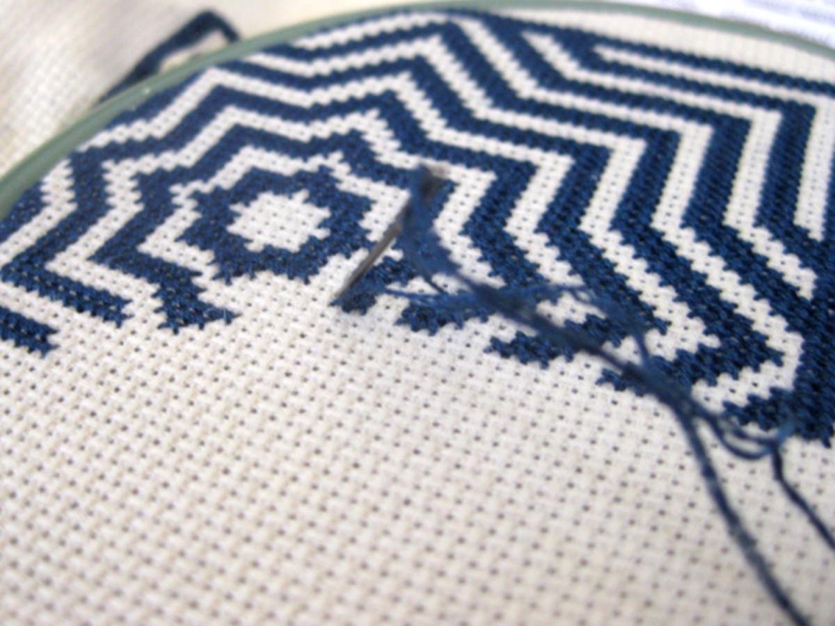 Sewing the biscornu cross stitch design onto Aida.