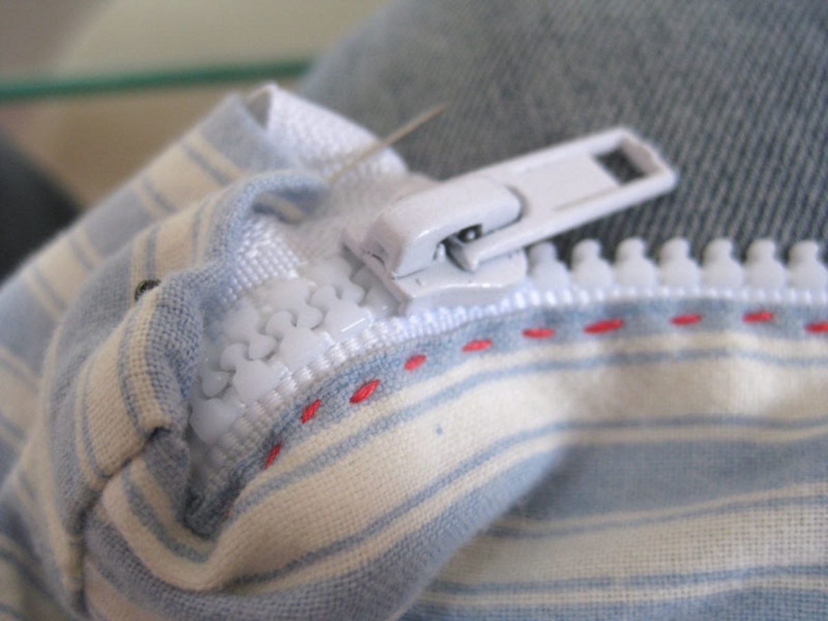 Stitch as far as you can until you cannot sew any further, due to the zip lump.