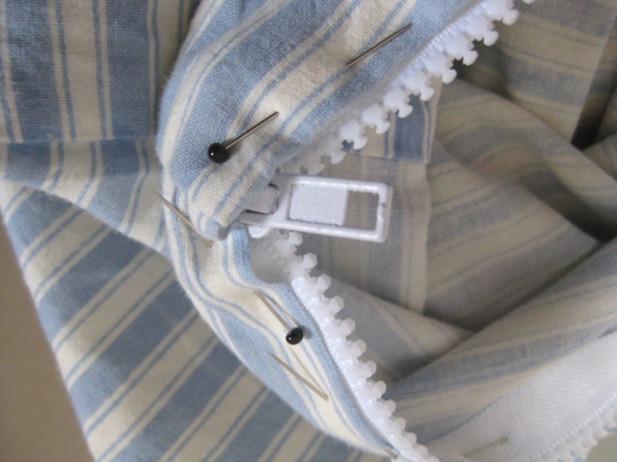 Pinning around the bottom end of the zip. Unzip until it reaches the end of the pillowcase (even if there is still some zip hanging off on the inside), then pin into place.