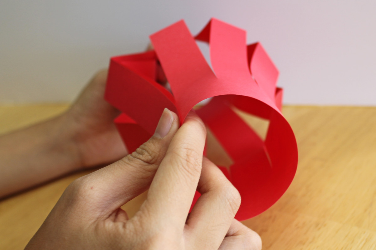 Once you have cut the paper for your Chinese lantern, open it up and bring the ends together to make a circle.