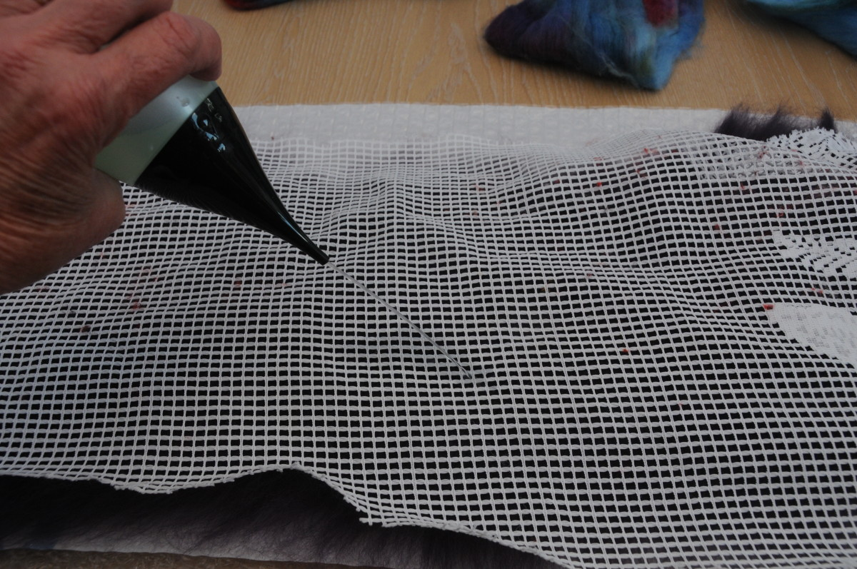 Cover with curtain netting. Wet and smooth down the fibers.  Remove the netting and turn the project over.