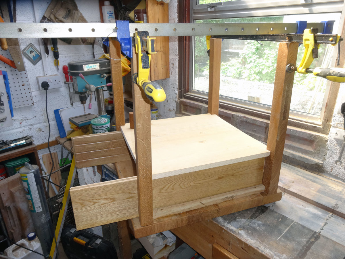 Using sash clamps to hold the legs in position when fixing the drawer support shelf and base.