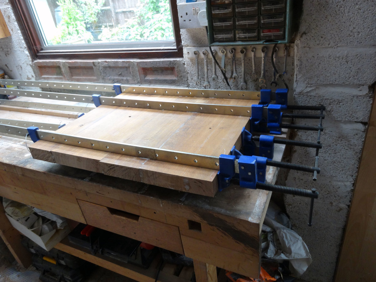 Clamping the planks together until the glued dowelled joints set.