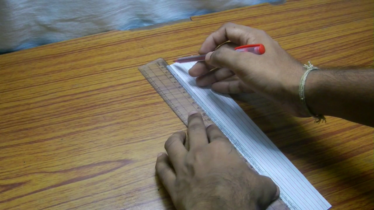 Now use a red pen to draw bricks of the paper house. For this, start by drawing parallel red lines with small gaps between them.