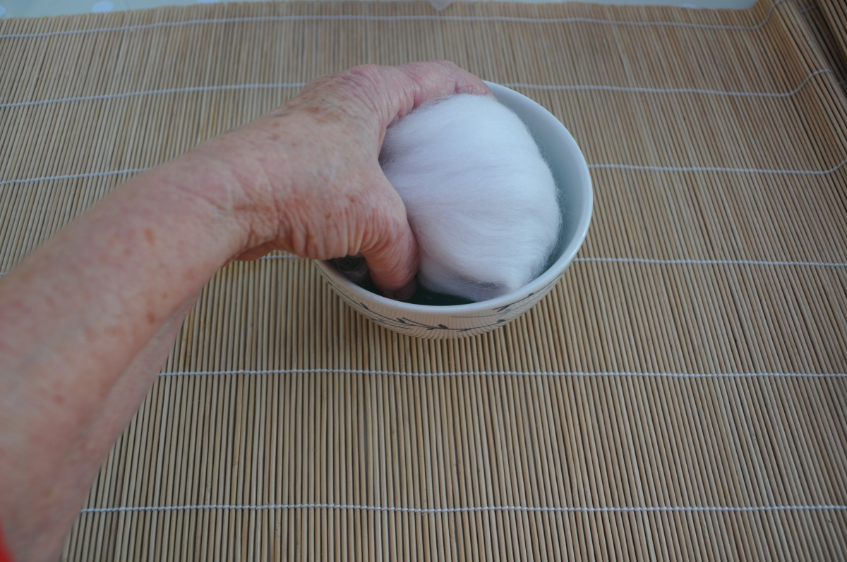 Wet all sides of the wool covered polystyrene ball by dipping each side lightly into the hot soapy water.