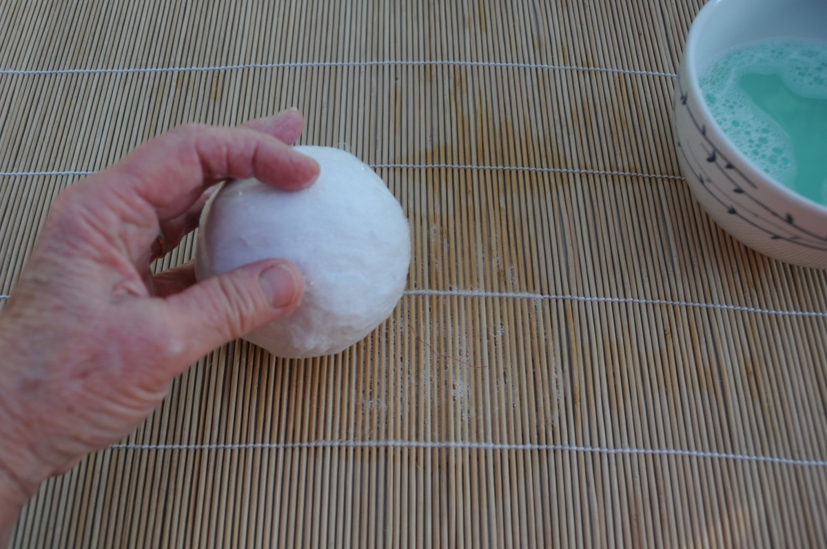 Roll the wool covered ball gently on the bamboo mat to smooth out the woolen Fibres.