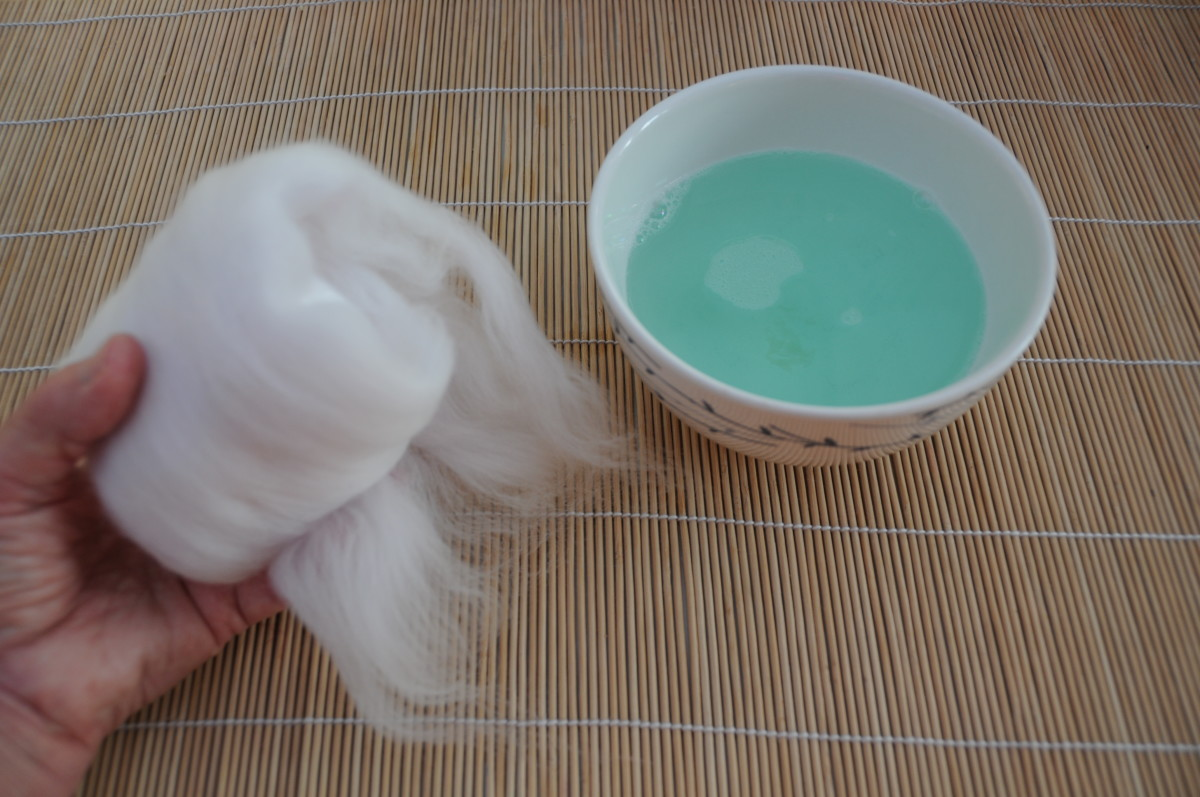 Wrap the white wool roving around the wet polystyrene ball.