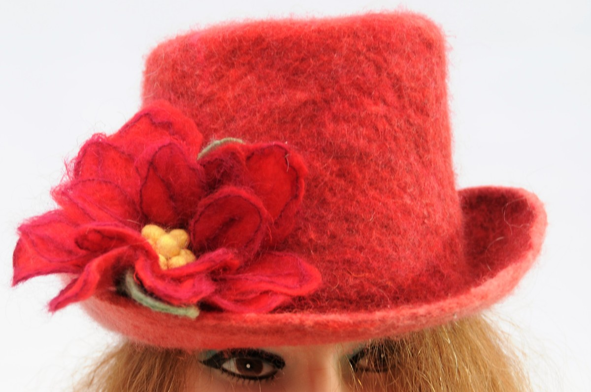 A red felt hat awaiting a hat band with the addition of a felt flower.